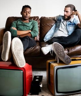 Deux homme assis et deux télévision rétro