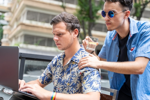Deux homme travaillant dans un ordinateur portable sur une terrasse portant un bracelet lgtb arc-en-ciel