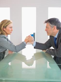 Deux hommes d'affaires agacés ayant un bras de fer assis autour d'une table