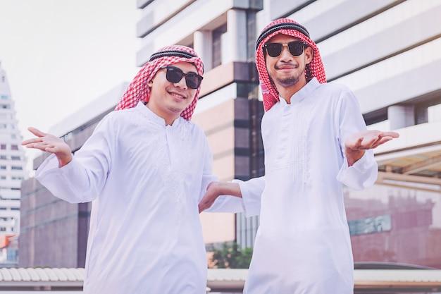 Deux hommes d'affaires arabes debout en levant les deux mains en ville
