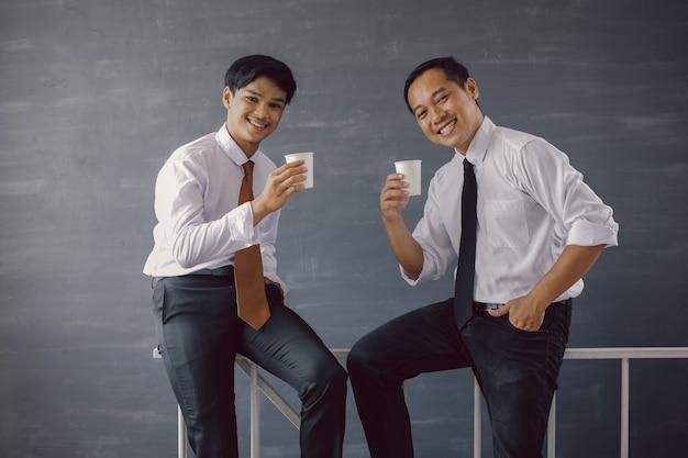 Deux hommes d'affaires asiatiques en chemise blanche et cravate souriant tout en offrant du café à la caméra