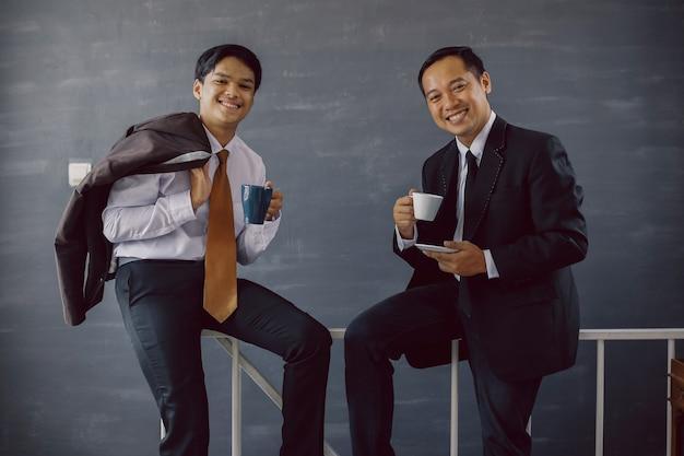 Deux hommes d'affaires asiatiques en costume souriant tout en offrant un café