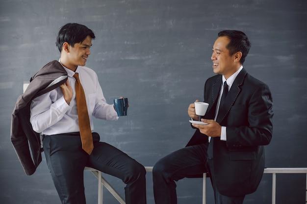 Deux hommes d'affaires asiatiques discutant tout en tenant un café pendant une pause