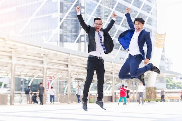 Deux hommes d'affaires asiatiques heureux travaillent dans la ville