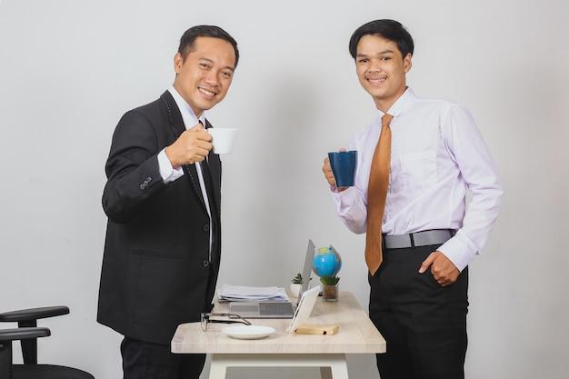 Deux hommes d'affaires asiatiques portant un costume et une cravate tenant une tasse et offrant du café à la caméra
