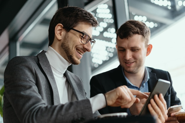 Deux hommes d'affaires ayant une conversation à l'aide d'un smartphone