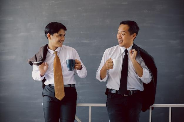Deux hommes d'affaires en chemises blanches et cravates discutant tout en tenant du café et des manteaux sur leur épaule