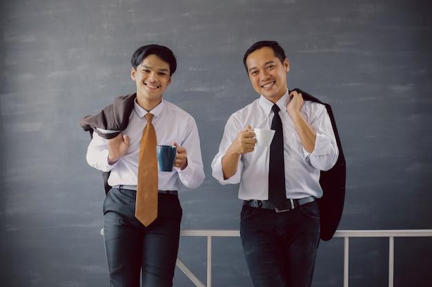 Deux hommes d'affaires en chemises et cravates souriant tout en offrant un café à la caméra