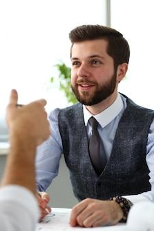 Deux hommes d'affaires de commis souriant délibèrent sur le problème au bureau