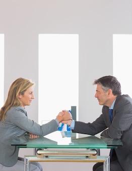 Deux hommes d'affaires de contenu ayant un bras de fer assis autour d'une table