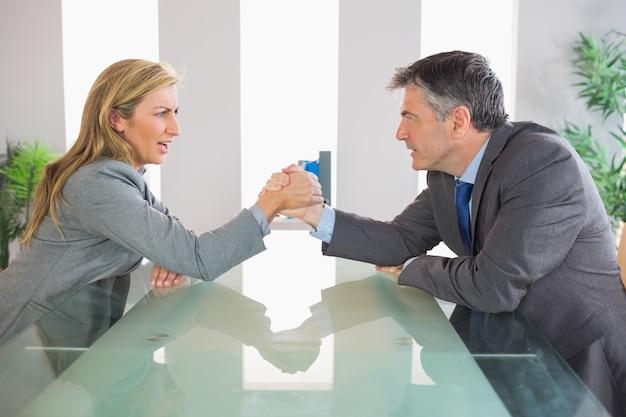 Deux hommes d'affaires contrariés ayant un bras de fer assis autour d'une table