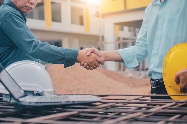 Deux hommes d'affaires équipe serrent la main accord projet de construction de bâtiments