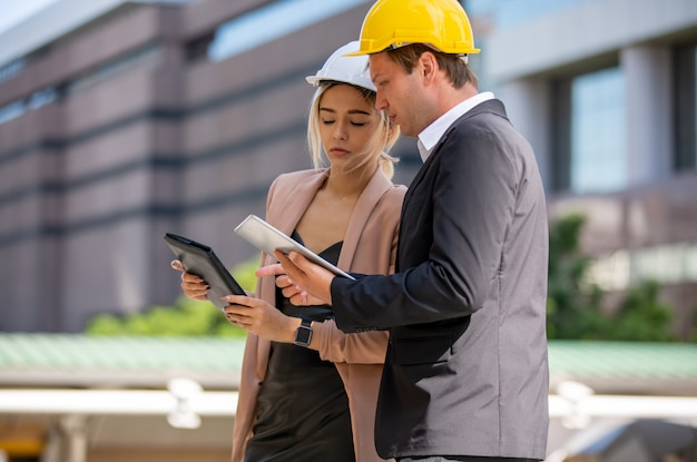 Deux hommes d'affaires et femme portant des gilets de sécurité parler et poignée de main sur chantier