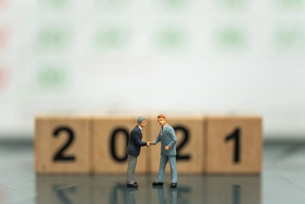 Deux hommes d'affaires figurines miniatures font une poignée de main avec un bloc en bois numéro 2021 et un calendrier en arrière-plan.