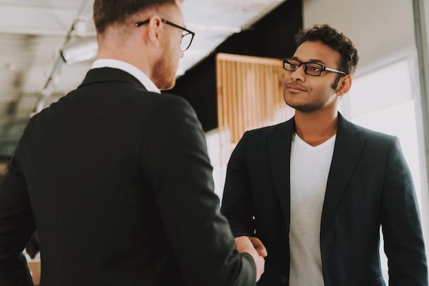 Deux hommes d'affaires à lunettes serre la main