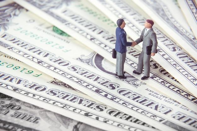 Deux hommes d'affaires miniatures se serrant la main en se tenant debout sur l'argent du dollar américain.