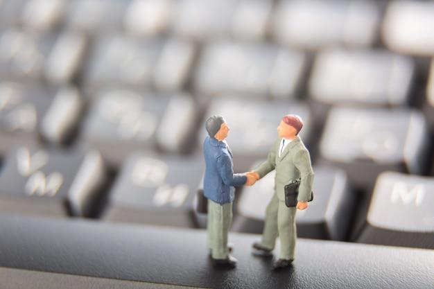 Deux hommes d'affaires miniatures se serrant la main en se tenant debout sur les touches d'un clavier noir.