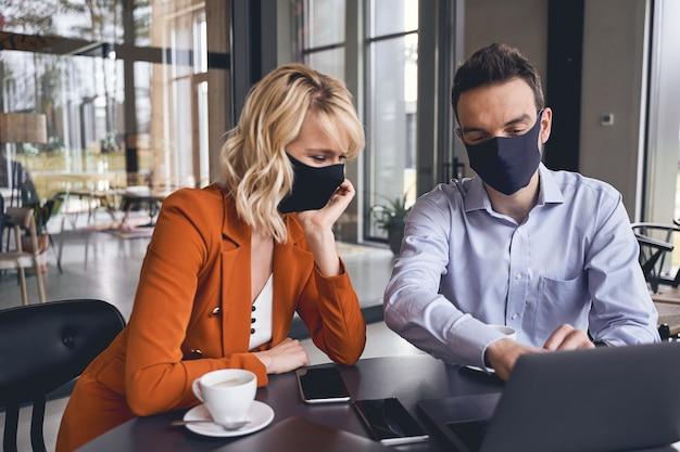 Deux hommes d'affaires modernes concentrés dans des masques faciaux assis au bureau du bureau