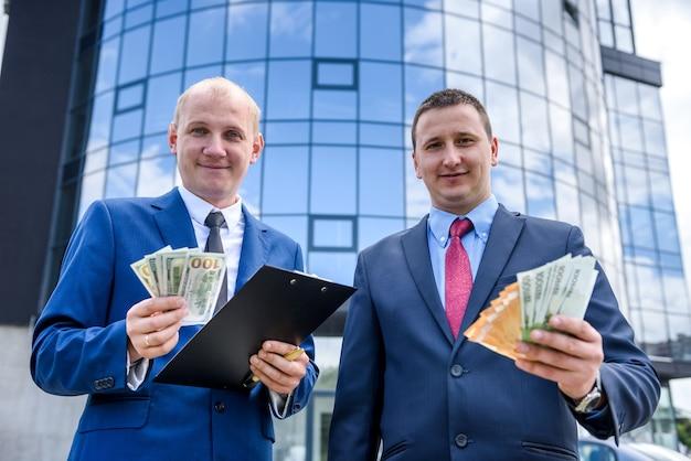 Deux hommes d'affaires montrant des billets en dollars et en euros
