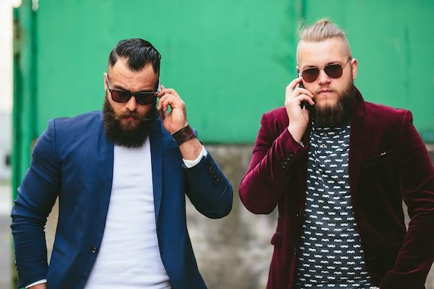 Deux hommes d'affaires parlant au téléphone dans la ville