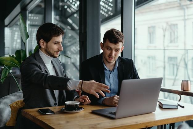 Deux, hommes affaires, pointage, ordinateur portable, écran, quoique, discuter