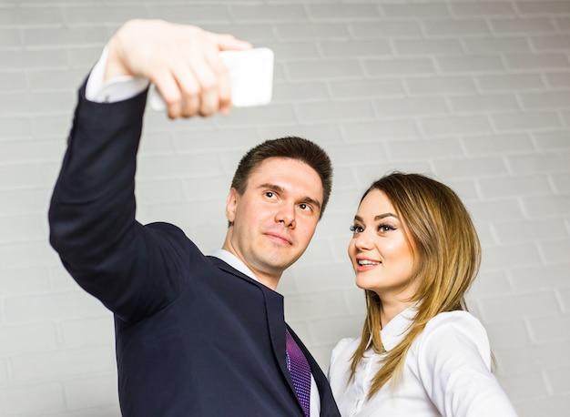 Deux hommes d'affaires prospères prenant un selfie heureux au bureau.