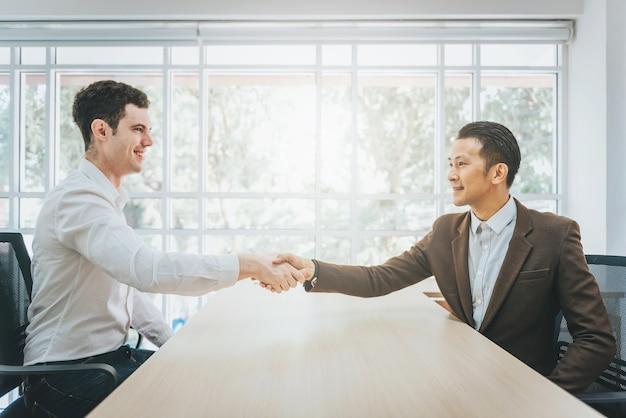 Deux hommes d'affaires se serrant la main dans un bureau