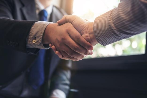 Deux hommes d'affaires se serrant la main lors d'une réunion pour signer un accord et devenir une entreprise pa