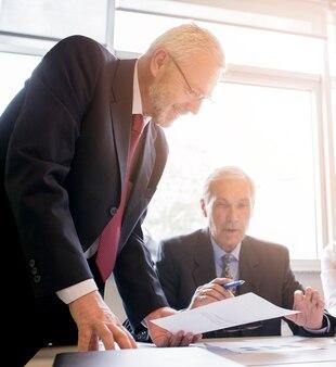 Deux hommes d'affaires senior discutant du document au bureau