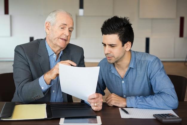 Deux hommes d'affaires sérieux inspectant le document