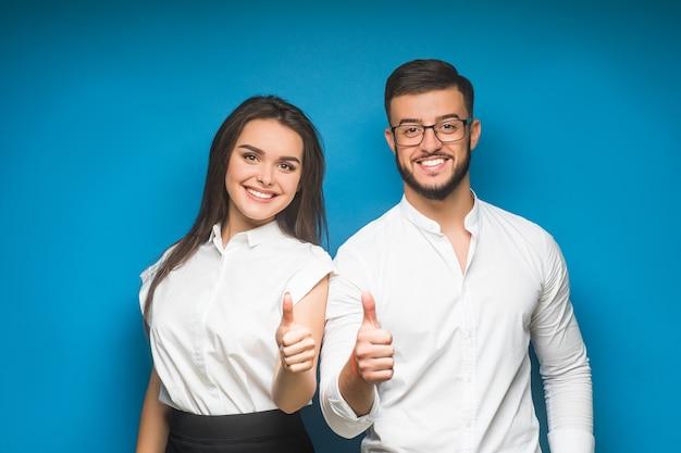 Deux hommes d'affaires souriants et confiants en tenues de soirée montrant un signe d'accord sur le bleu
