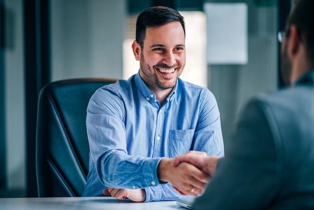 Deux hommes d'affaires souriants se serrant la main tout en étant assis au bureau.