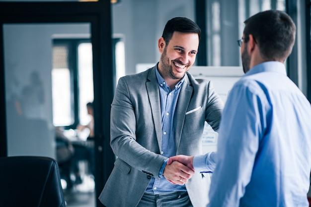 Deux hommes d'affaires souriants se serrant la main tout en se tenant dans un bureau.
