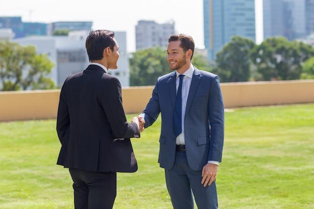 Deux hommes d'affaires souriants secouant les mains à l'extérieur