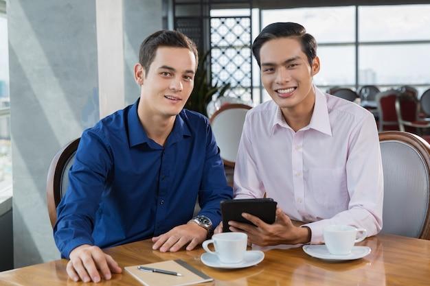 Deux hommes d'affaires, sourire, travailler sur l'ordinateur tablet