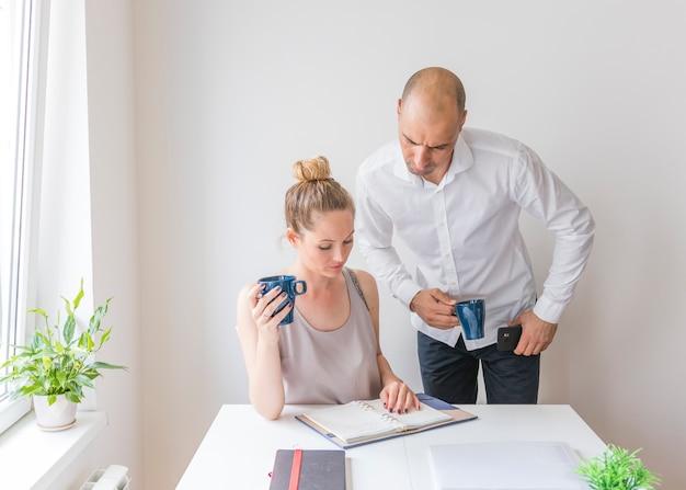 Deux hommes d'affaires tenant une tasse de café en regardant l'agenda