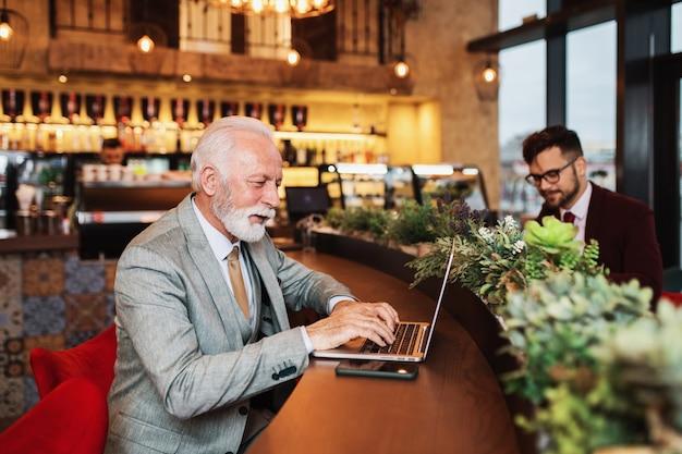 Deux hommes d'affaires travaillant ensemble dans un café moderne.
