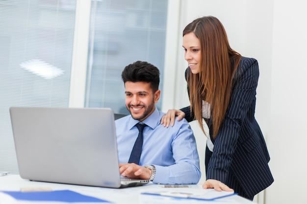 Deux hommes d'affaires travaillant avec un ordinateur portable