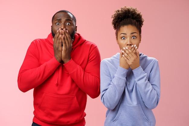 Deux hommes afro-américains choqués écarquillent les yeux inquiets terriblement désolés presse paumes bouche haletant témoin catastrophe entendre triste mauvaise nouvelle, debout inquiet fond rose ami sympathisant