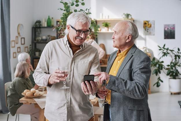 Deux hommes âgés tenant des verres de vin rouge à l'aide d'un téléphone portable et discutant du travail en ligne