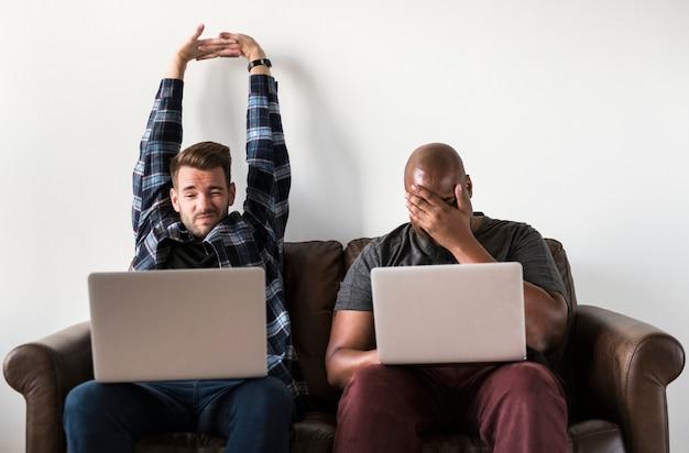 Deux hommes à l'aide d'un ordinateur portable assis sur un canapé