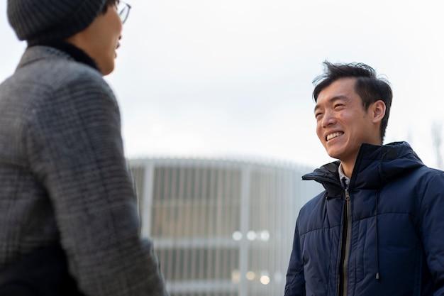 Deux hommes asiatiques attrayants souriant et se parlant. en plein air