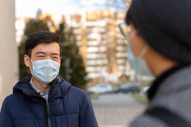 Deux hommes asiatiques dans des masques médicaux contre les sourires de covid-2019 et se parlent