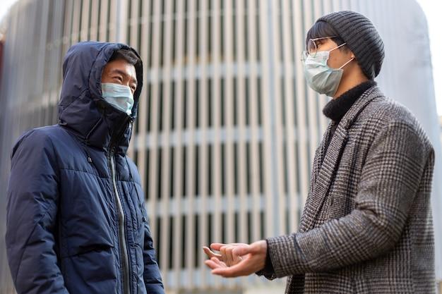 Deux hommes asiatiques dans des masques médicaux faciaux. à l'extérieur. covid-2019. protection contre le virus