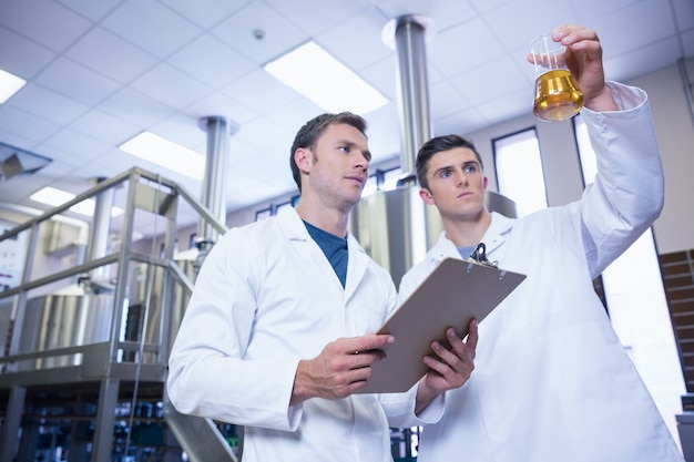 Deux hommes en blouse de laboratoire regardant le bécher avec de la bière