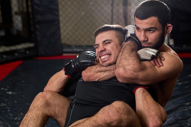 Deux hommes boxeurs en gants se battent au gymnase à l'aide de grappling, assis allongé sur un tapis dans un ring au gymnase. concept de kickboxing et de sport