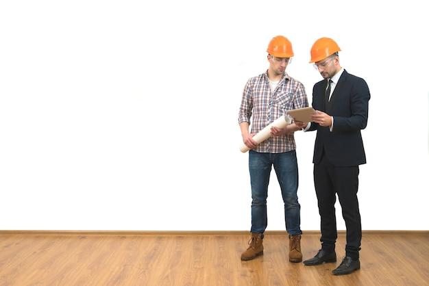 Les deux hommes en casques se tiennent avec une tablette sur le fond du mur blanc