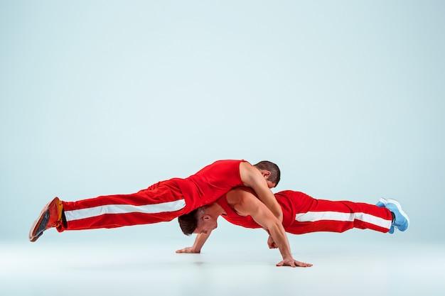 Deux hommes caucasiens acrobatiques de gymnastique en équilibre posent