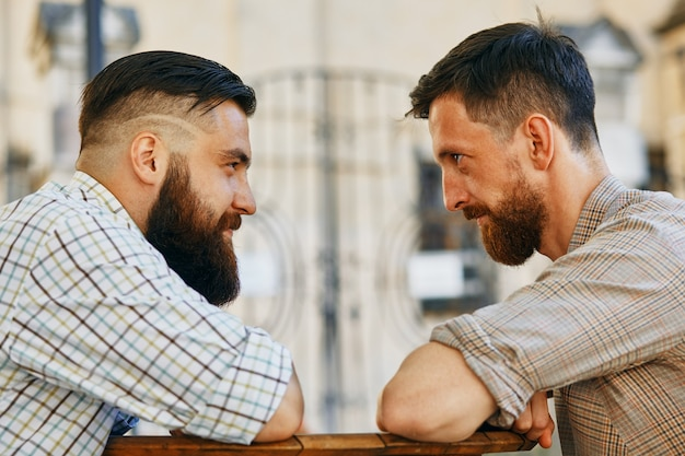 Deux hommes communiquent avec leurs points de vue à la table