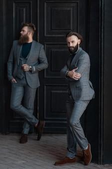 Deux hommes en costumes gris contre une porte noire